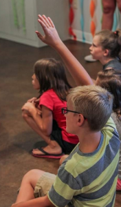 Child raising his hand for a question.